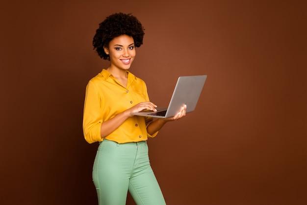 아름 다운 어두운 피부 비즈니스 레이디의 프로필 사진 노트북을 들고 기업 정보 쓰기 이메일 착용 노란색 셔츠 녹색 바지 절연 갈색 색상