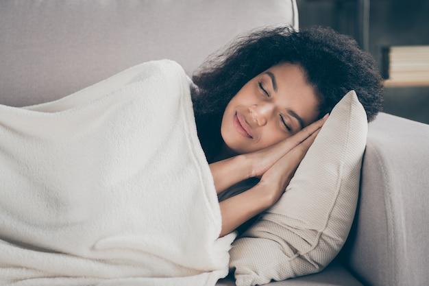 目を閉じて手をつないで美しい暗い肌の波状の女性のプロフィール写真は、屋内の白い柔らかい毛布のリビングルームで覆われた快適なソファに横たわっている空想を持っています