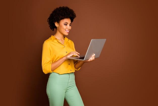 아름 다운 어두운 피부 물결 모양의 여자의 프로필 사진 노트북 손을 잡고 기업 정보 쓰기 이메일 착용 노란색 셔츠 녹색 바지 절연 갈색 색상