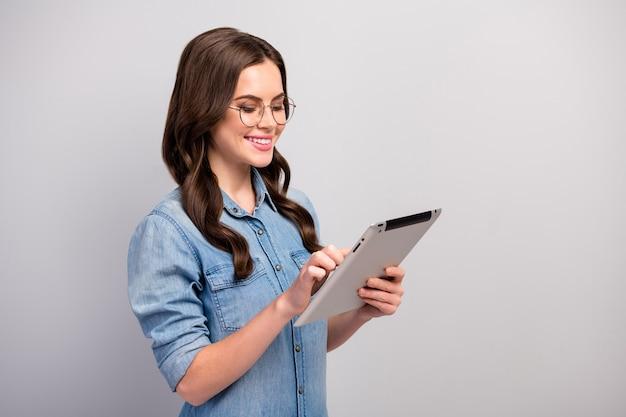 Фотография профиля красивой девушки-фрилансера, держащей планшет для чтения электронных книг, ищет информацию, читает рабочий отчет, спецификации одежды повседневные джинсы джинсовая рубашка изолирована серого цвета