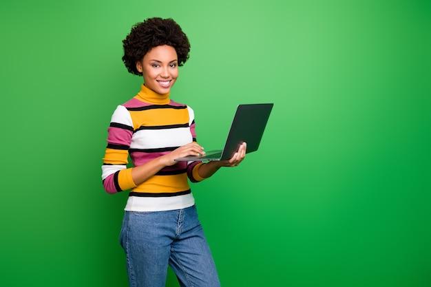美しいかなり暗い肌のカーリーレディホールドノートブックのプロフィール写真ニュースを読むプロの歯を見せる笑顔ウェアカジュアルストライププルオーバージーンズ