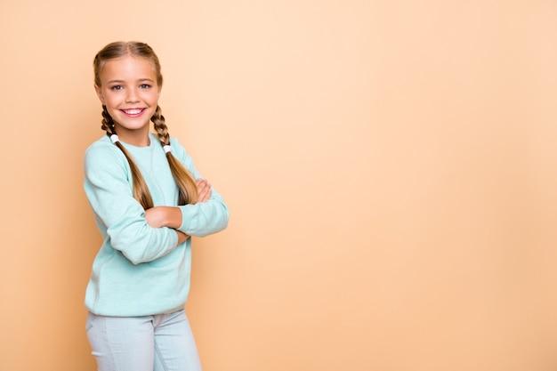 Фотография профиля красивой симпатичной маленькой дамы, скрестив руки, лучшая ученица школы, показывающая пустое пространство, баннерная реклама, носить синие джинсы-пуловеры, изолированные на бежевой стене в пастельных тонах