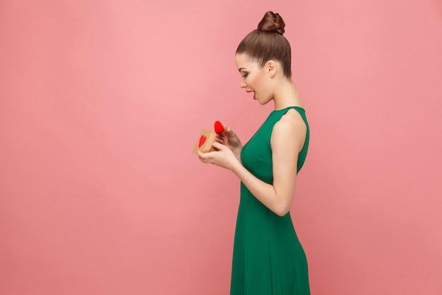 ハートのギフトボックスを保持している美しい女性のプロフィール写真