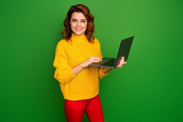 Фотография профиля жизнерадостной бизнес-леди, держащей ноутбук за руки, просматривающей внештатный ит-администратор веб-сайта в желтом вязаном пуловере, красные штаны, изолированные на стене зеленого цвета
