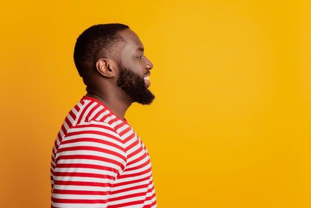 陽気な暗い肌の男のプロフィール写真は空のスペースに見える歯を見せる晴れやかな笑顔