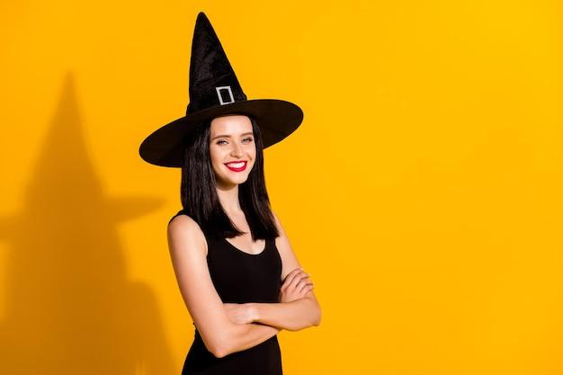 かわいい素敵な若い魔術師の女性のプロフィール写真腕を組んで輝く光沢のある笑顔がテーマカーニバルイベントに参加する黒い帽子のドレスを着用して明るい黄色の背景を分離しました