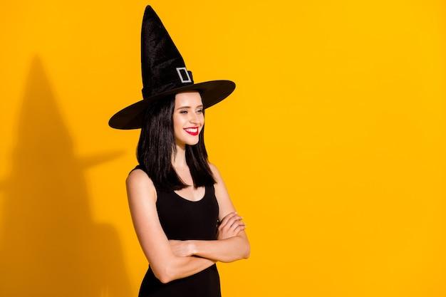 かわいい素敵な若い魔術師の女性のプロフィール写真交差した腕は空のスペースを見て晴れやかな笑顔のロールプレイイベント着用黒の帽子ドレス孤立した明るい黄色の色の背景