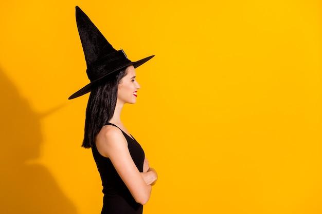 かわいい素敵な若い魔術師の女性のプロフィール写真は、笑顔を輝かせて手を交差させた準備入力魔女の女優キャスティングウェア黒の帽子ドレス孤立した明るい黄色の色の背景