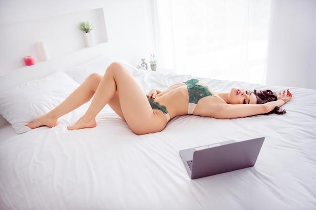 장난 꾸러기 아름다운 여성 집 검역 온라인 노트북 채팅 카메라에 자위하는 다리 사이에 자신을 만지는 아름다운 여성의 프로필 사진 혼자 비키니를 입고 실내에 앉아 흰색 린넨 시트