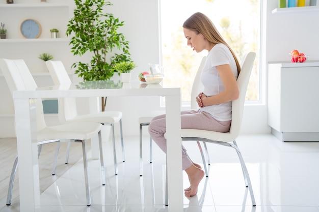 ひどい痛みに苦しんでいる腹を抱えているかわいい主婦のプロフィール写真は牛乳を食べることができません朝食コーンフレークは胃が動揺している座っているテーブル白い光のキッチン屋内