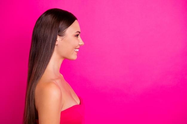 긴 헤어 스타일과 빈 공간에 관심이있는 매력적인 미소를 가진 예쁜 아가씨의 프로필 사진은 오프 숄더 탑 절연 생생한 핑크색 배경을 착용합니다.