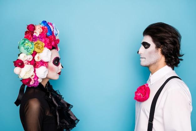 怖い二人のプロフィール写真男性女性は真剣に目を見る血まみれの犠牲の儀式を準備する黒いドレス死の衣装バラヘッドバンドサスペンダー孤立した青い色の背景