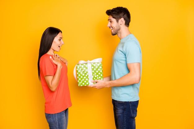 Фотография в профиле двух парней, леди, держащихся за руки, большая подарочная коробка, романтический сюрприз на 8 марта, носить повседневные модные сине-оранжевые футболки, джинсы, изолированные на стене желтого цвета