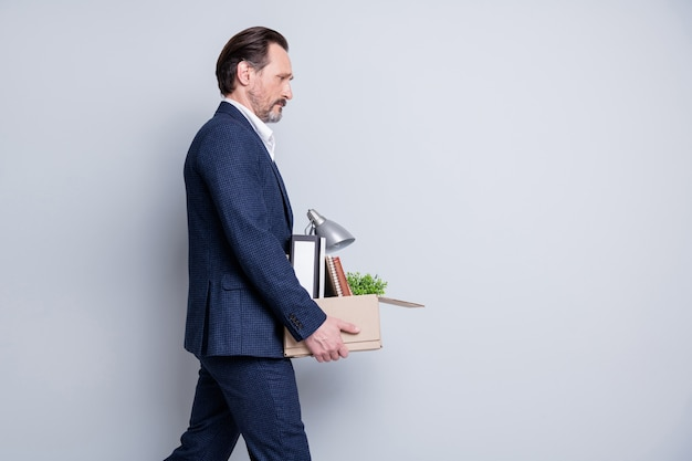 불행한 스트레스를 받는 성숙한 남자 실업자 희망 없는 금융 위기의 프로필 사진 사무실에서 피곤한 산책을 끝내고 해고된 판지 상자 소지품을 들고 격리된 회색 배경