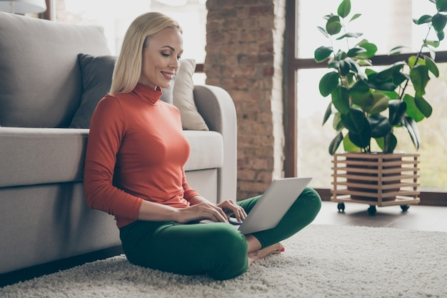 Profile photo of pretty business lady domestic mood working home writing report notebook sitting comfy carpet floor near couch casual outfit living room indoors