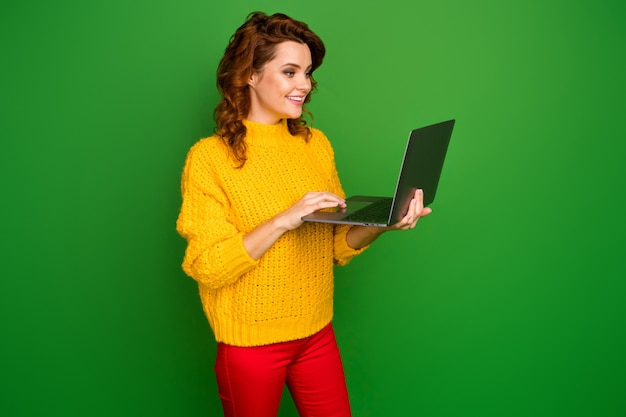 Profile photo of pretty cheerful lady hold notebook hands browsing freelance it website administrator wear yellow knitted sweater red pants isolated green color wall