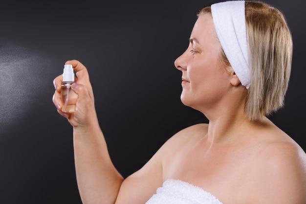 プロフィール写真。彼女の頭に包帯を巻いた年配の女性は、黒い背景にスプレーをスプレーします。高品質の写真