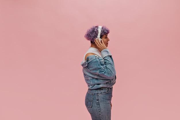 Foto del profilo di una donna con i capelli viola e vestiti di jeans moderni. la donna meravigliosa in cuffie bianche gode di ascoltare la musica.