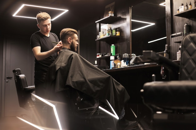 Profile photo of a young barber trimming his customerã¢â€â™s hair with an electric shaver and a comb in a barbershop.
