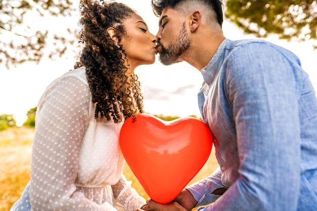 彼らの間で赤いハート型の風船に太陽のバックライト効果で自然の中で日没にキスする愛の多民族カップルのプロフィール写真。 2人の異性愛者の若者の夕暮れ時のロマンチックなシーン