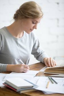 Profile portait of girl performing a written task in copybook
