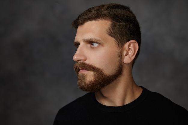 Profile portrait of attractive macho man with neat trimmed beard and mustache posing isolated at blank wall, frowning, expressing suspicion, looking away, having strict serious expression