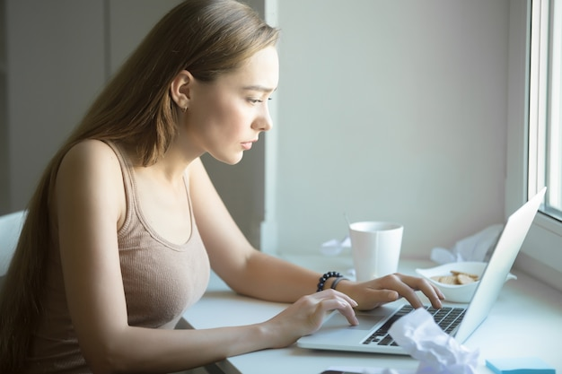 Profile portrait of attractive woman working on a laptop