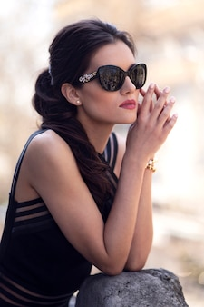 Profile portrait of a beautiful, brunette young woman wear black sunglasses and dress, hair ponytail and makeup, posing at the balcony in the sunny day.