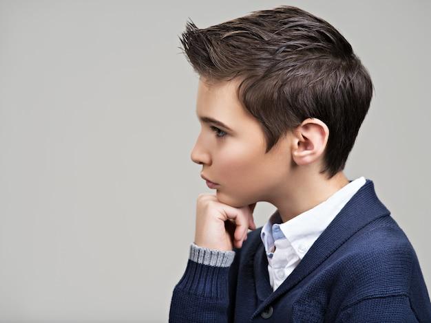 Profile portrait of a beautiful teenage boy posing at studio as a fashion model.
