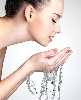 Profile portrait of beautiful woman washing face with water