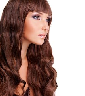 Ritratto di profilo di bella donna con lunghi capelli rossi. fronte del primo piano con l'acconciatura riccia, isolata su bianco.