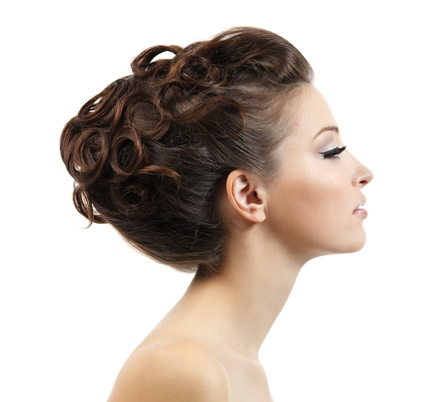 Profile portrait of the beautiful young girl with curly hairstyle on white
