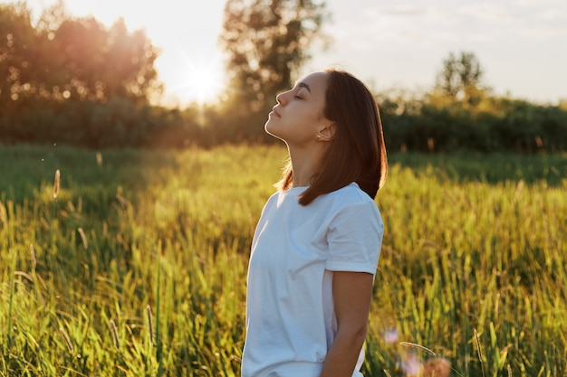 Profile portrait of brunette female wearing white casual style attire posing in green field on sunset, keeping eyes closed, enjoying beautiful nature and freedom.
