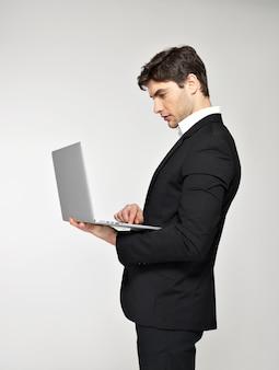 Profile portrait of businessman working on laptop in black suit