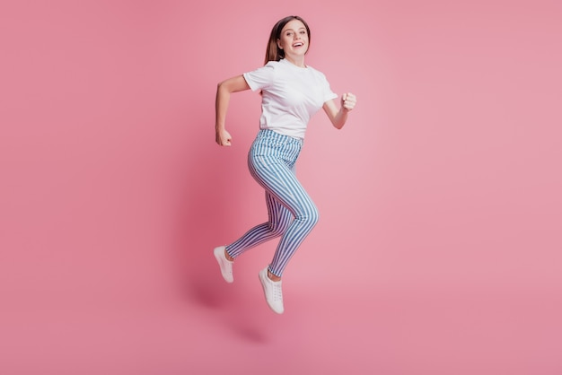 Profile portrait of cheerful funny girl jumping in the air wear casual denim outfit on pink wall