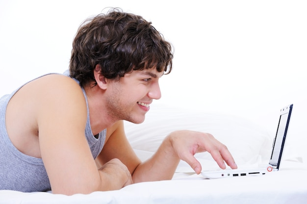 Profile portrait of a cheerful young male typing on laptop lying in his bed