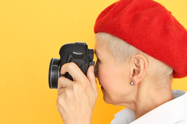 Profile portrait of creative stylish short haired middle aged woman photographer in red bonnet posing against yellow background with professional digital camera in her hands. art photography