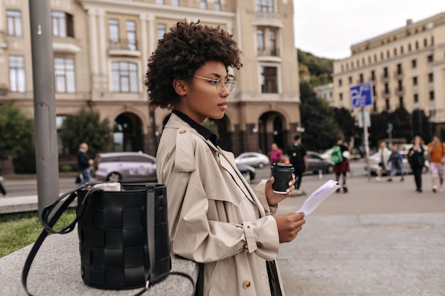 Profile portrait of curly dark-skinned woman holding paper sheet and coffee cup