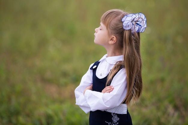 Profile portrait of cute adorable first grader girl in school uniform and white bows