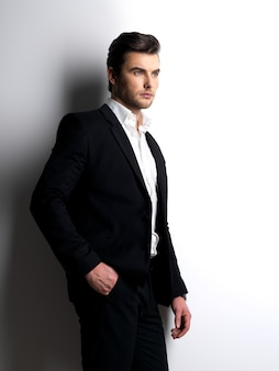 Profile portrait of a fashion young man in black suit posing at  studio