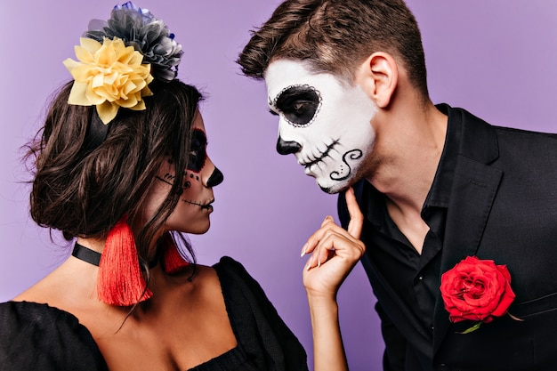 Profile portrait of girl with bright colorful accessories and her man in black jacket with rose in his pocket, looking at each other.