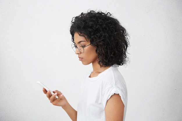 Profile portrait of good-looking attractive black mixed race female in round glasses, holding white smartphone in hand and using it with serious face expression, searching for important information