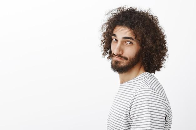 Ritratto di profilo di un bel ragazzo dai capelli ricci con la barba, sorridente con espressione amichevole compiaciuta