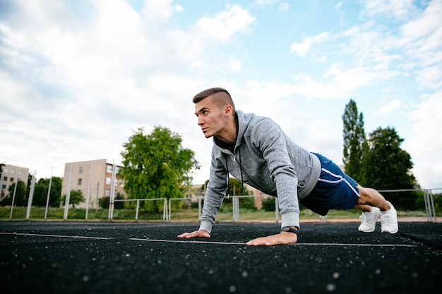 Profile portrait of handsome man practising exercise, dressed in sportswear, outdoors