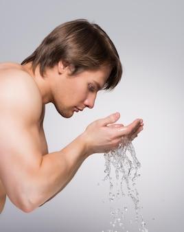 Ritratto di profilo di un uomo bello che si lava il viso con acqua sul muro grigio.