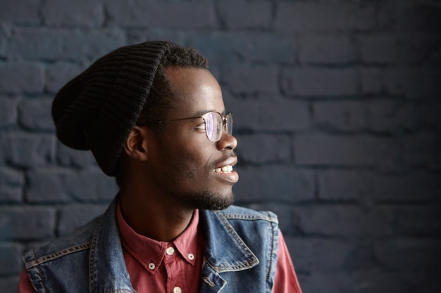 Profile portrait of handsome stylish young afro-american male wearing glasses