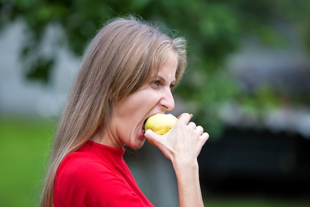 Profile portrait of moody upset angry young woman biting apple.