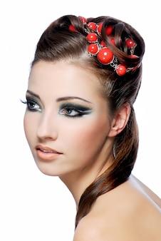 創造性のヘアスタイルとスタイリッシュなメイクで魅力的な若い女性のプロフィールの肖像画