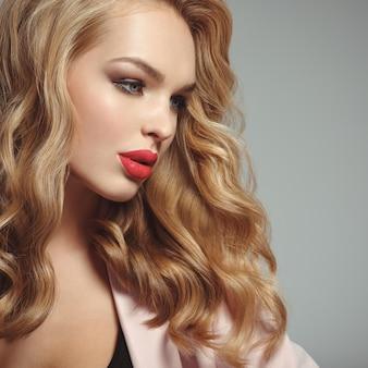섹시 한 붉은 입술으로 아름 다운 젊은 금발 여자의 프로필 초상화. 긴 곱슬 머리를 가진 매력적인 소녀. 스모키 아이 메이크업