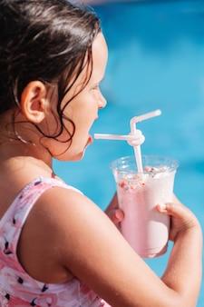 海沿いのビーチでストローからカクテルを飲む白人の女の子のプロフィールの肖像画...